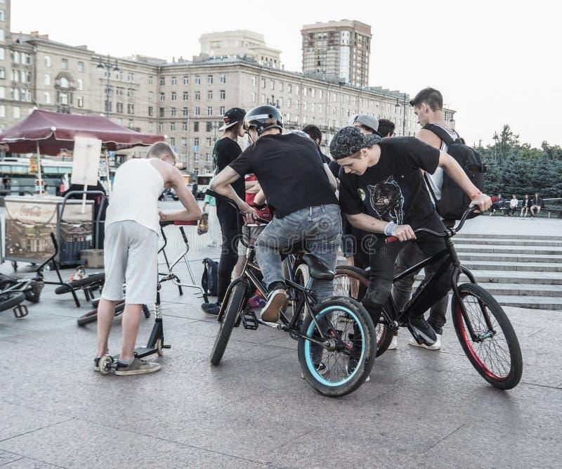 Mensen die, de ontmoetingsplaats van de fietserstroep ongeveer hangen Jonge jongens die uit op een vleetplaats hangen Rusland Hei stock foto's