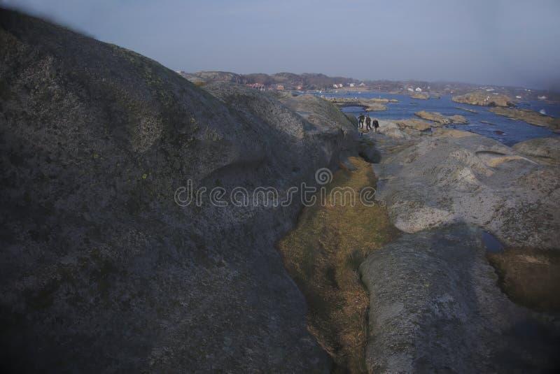 Mensen die de rotsen en het mos op eiland beklimmen stock afbeeldingen