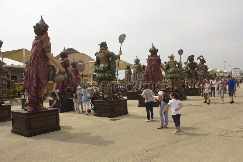 Mensen die de standbeelden van voedselstrijders voor Expo-ingang waarnemen royalty-vrije stock foto's