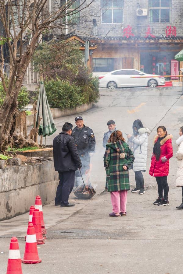 Mensen die dichtbij een brand opwarmen stock foto's