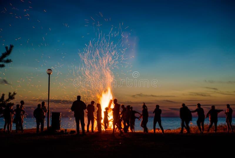 Mensen die dichtbij groot vuur rusten openlucht stock afbeeldingen