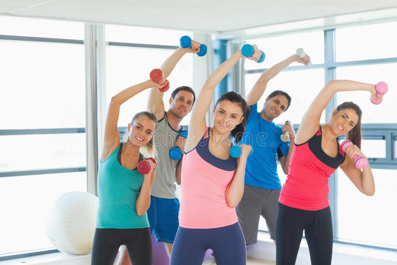 Mensen die domoorgewichten met trainer in gymnastiek opheffen stock fotografie