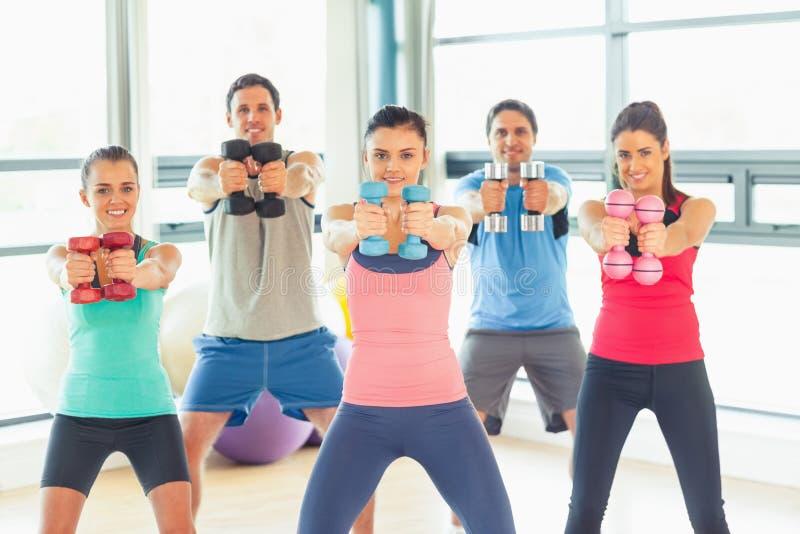 Mensen die domoorgewichten met trainer in gymnastiek opheffen royalty-vrije stock foto's