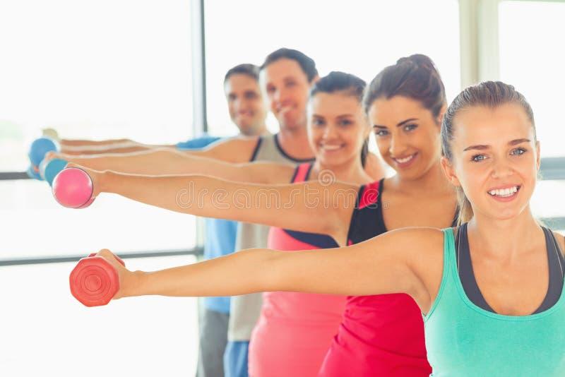 Mensen die domoorgewichten met trainer in gymnastiek opheffen stock foto