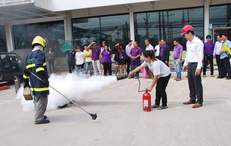 Mensen die een brandoefening uitoefenen die een brand met een poedertype brandblusapparaat doven royalty-vrije stock foto
