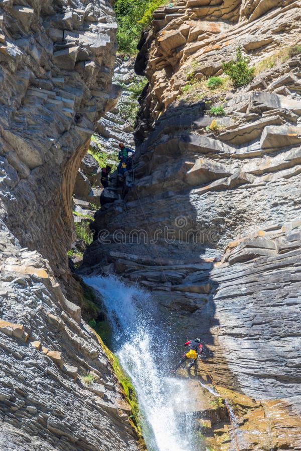 Mensen die in een indrukwekkende waterval rappelling stock afbeeldingen