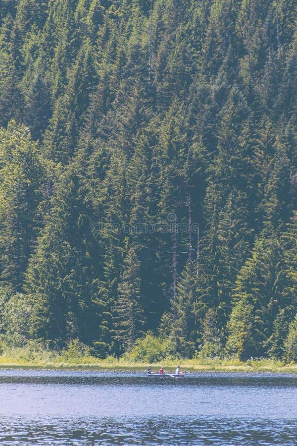 Mensen die een kleine boot in een meer met een mooi bos op de achtergrond roeien royalty-vrije stock fotografie