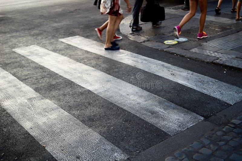 3 mensen die een witte Gestreepte Kruising, op een grijze tarmacweg kruisen, in Centraal Rome Italië stock foto's