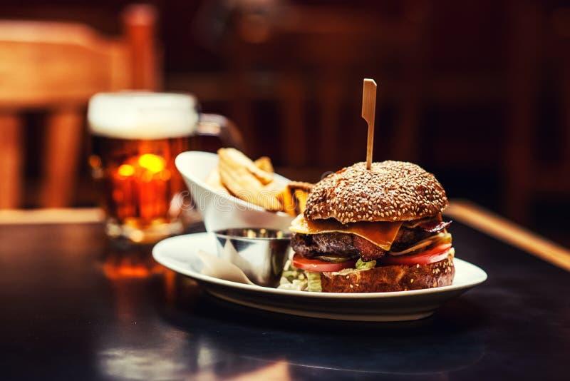 Mensen die en in Amerikaans restaurant, bier, hamburger, wijn en andere Amerikaanse specialites eten drinken stock foto