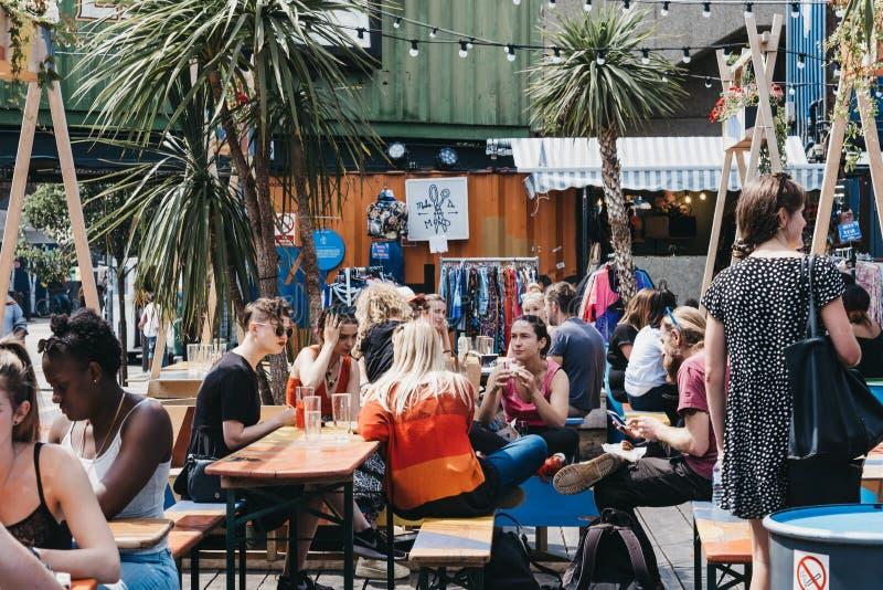 Mensen die en bij de lijstenbinnenkant Pop eten drinken Brixton, Londen, het UK stock foto
