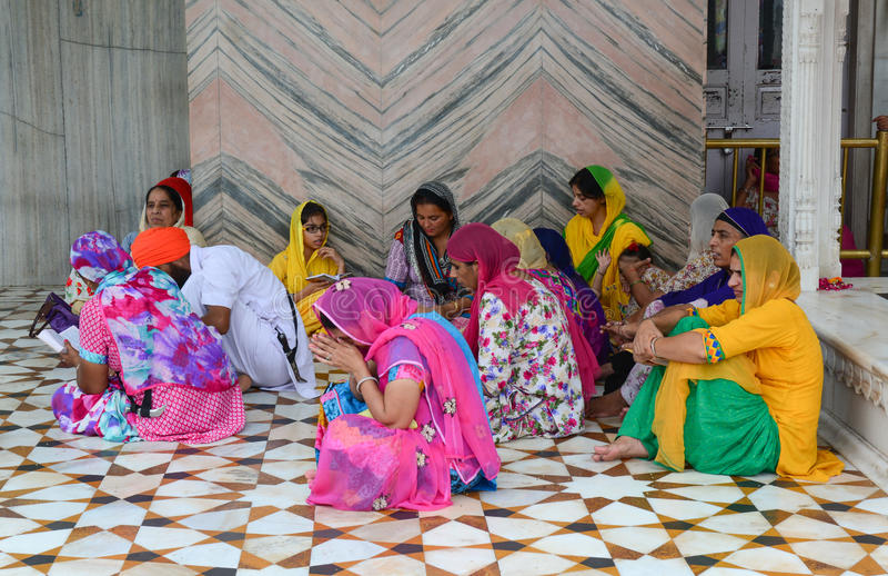 Mensen die en bij Gouden tempel in Amritsar, India zitten bidden stock afbeeldingen