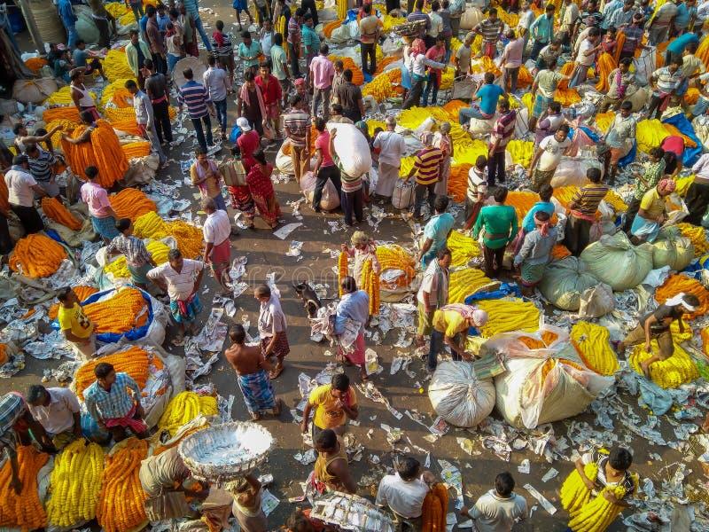 Mensen die en bloemen en slingers kopen verkopen bij de bloemmarkt dichtbij mullick stock foto