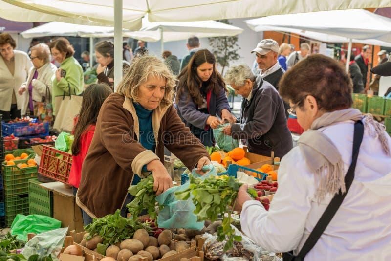 Mensen die en een traditionele landbouwersmarkt in Portugal, Europa verkopen inkopen stock foto's