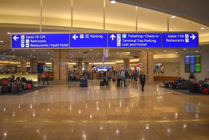 Mensen die, en met bagagges rusten lopen Poorten, Parkeren, Etiketterings en Controleteken in Orlando International Airport royalty-vrije stock foto's