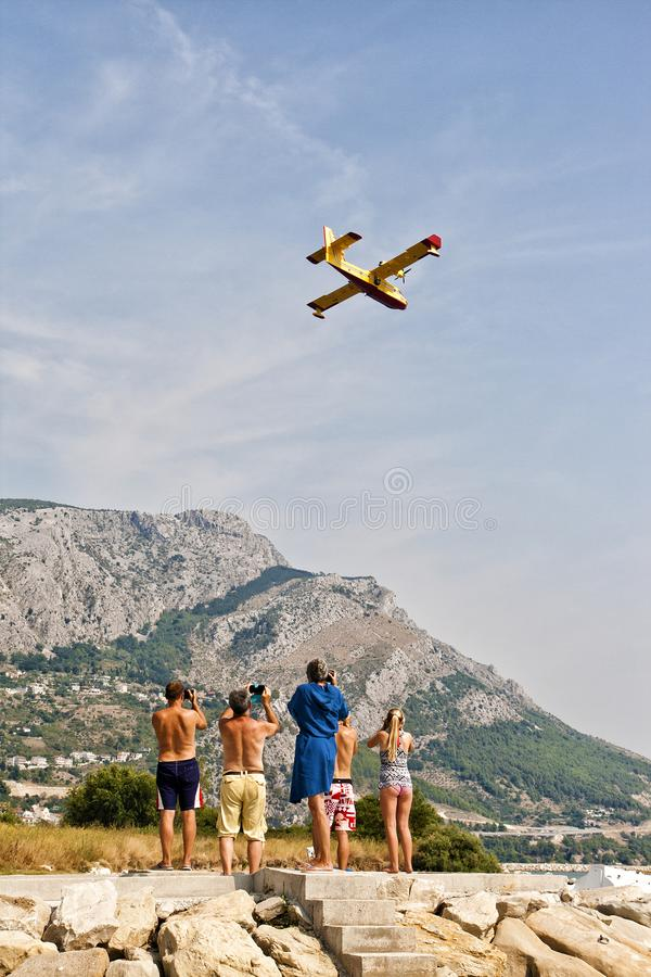 Mensen die en op foto's van brandbestrijdersvliegtuig letten maken in actie royalty-vrije stock fotografie