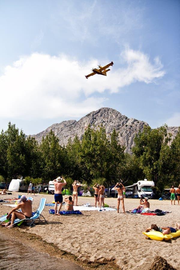 Mensen die en op foto's van brandbestrijdersvliegtuig letten maken in actie stock foto's