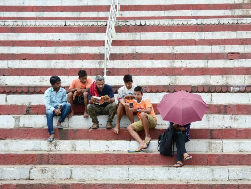 Mensen die en op straat in Varanasi, India zitten babbelen stock fotografie