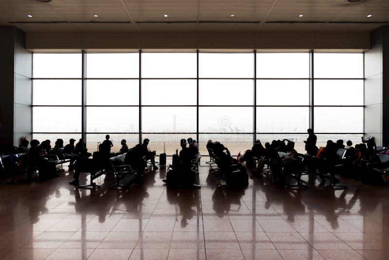 Mensen die en op vertrek in luchthaven zitten wachten royalty-vrije stock fotografie