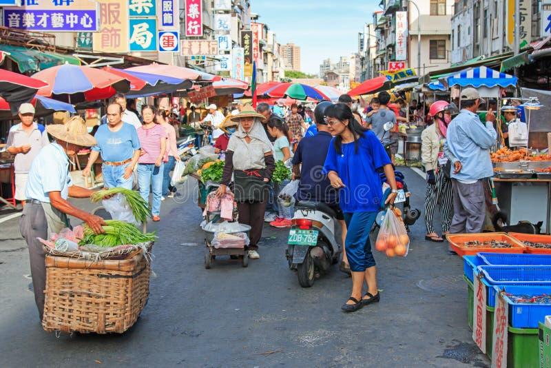 Mensen die en voedsel in een traditioneel fruit en een plantaardige markt van Taiwan verkopen kopen royalty-vrije stock afbeelding