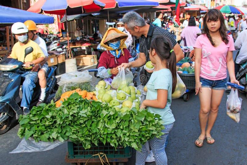 Mensen die en voedsel in een traditioneel fruit en een plantaardige markt van Taiwan verkopen kopen stock afbeeldingen