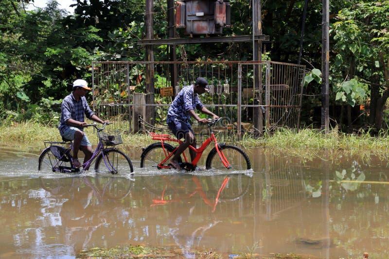 Mensen die fietsen berijden op de overstroomde wegen stock afbeelding