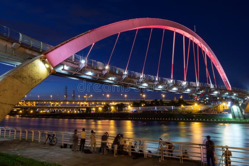 Mensen die foto's van een aangestoken brug in Taipeh nemen bij avond stock fotografie