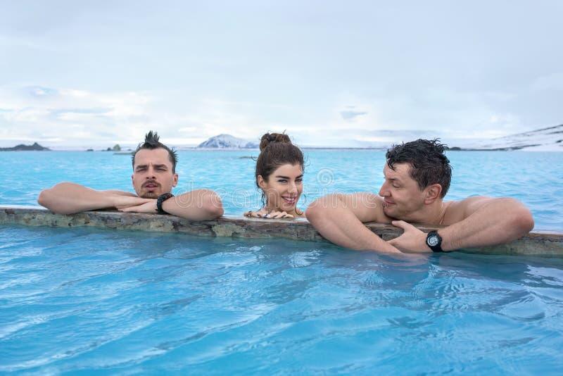 Mensen die in geothermische pool in openlucht ontspannen stock afbeeldingen