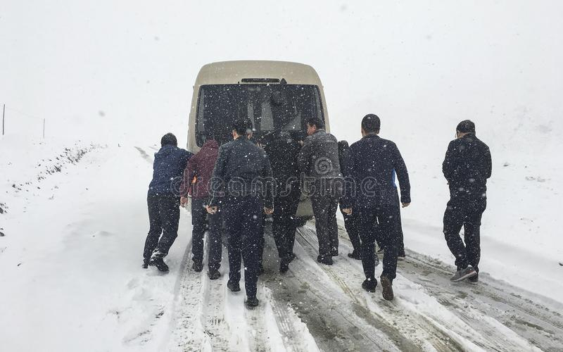 Mensen die geplakte auto in sneeuwberg duwen royalty-vrije stock afbeeldingen