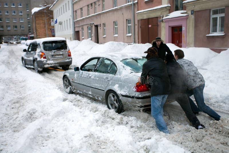 Mensen die geplakte auto in sneeuwstraat duwen stock fotografie