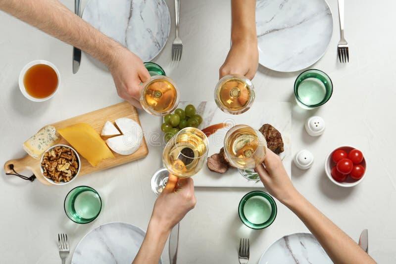 Mensen die glazen witte wijn over lijst met smakelijke snacks houden stock afbeelding
