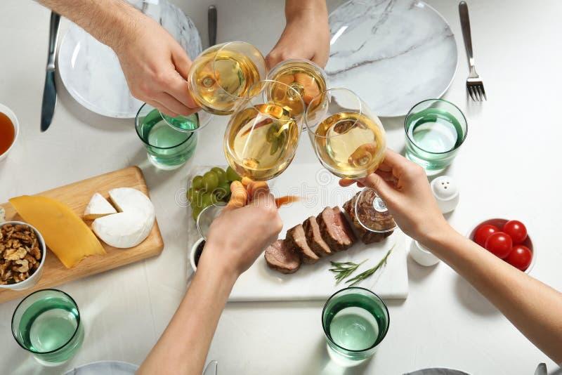 Mensen die glazen witte wijn over lijst met smakelijke snacks houden stock foto's