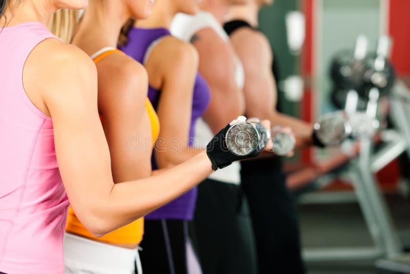 Mensen die in gymnastiek met domoren uitoefenen royalty-vrije stock afbeeldingen
