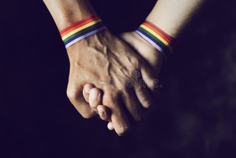 Mensen die handen met regenboog-gevormde manchet houden royalty-vrije stock afbeelding