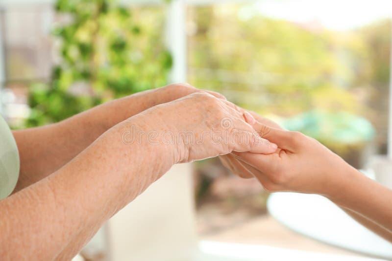 Mensen die handen samen op vage achtergrond houden Hulp en bejaard zorgconcept royalty-vrije stock fotografie