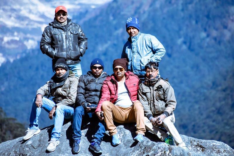Mensen die het bereiken bovenop een berg vieren stock foto