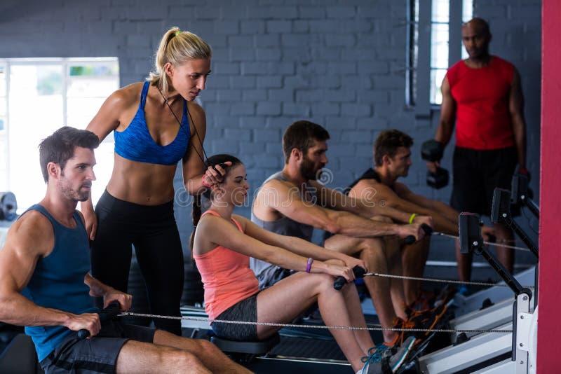 Mensen die het roeien machine met geschiktheidsinstructeur met behulp van in gymnastiek stock afbeeldingen
