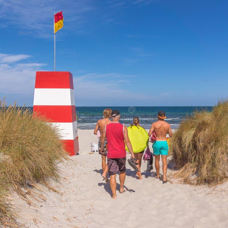 Mensen die in het zand naar het overzees en een rescuetower lopen royalty-vrije stock foto