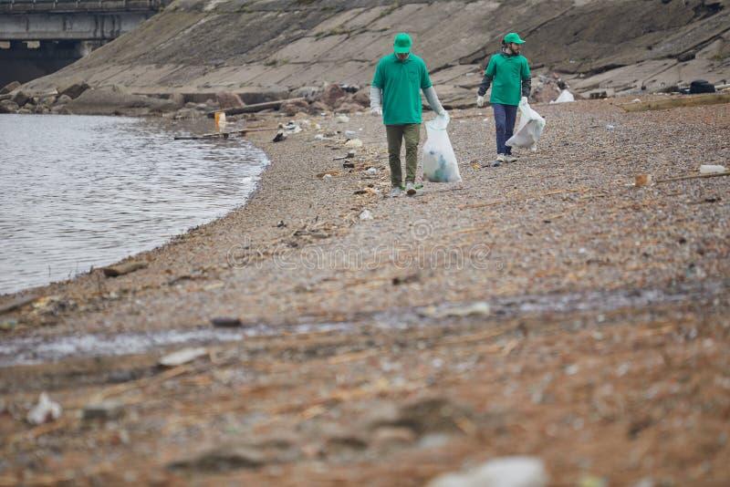 Mensen die huisvuil op kust verzamelen stock afbeelding