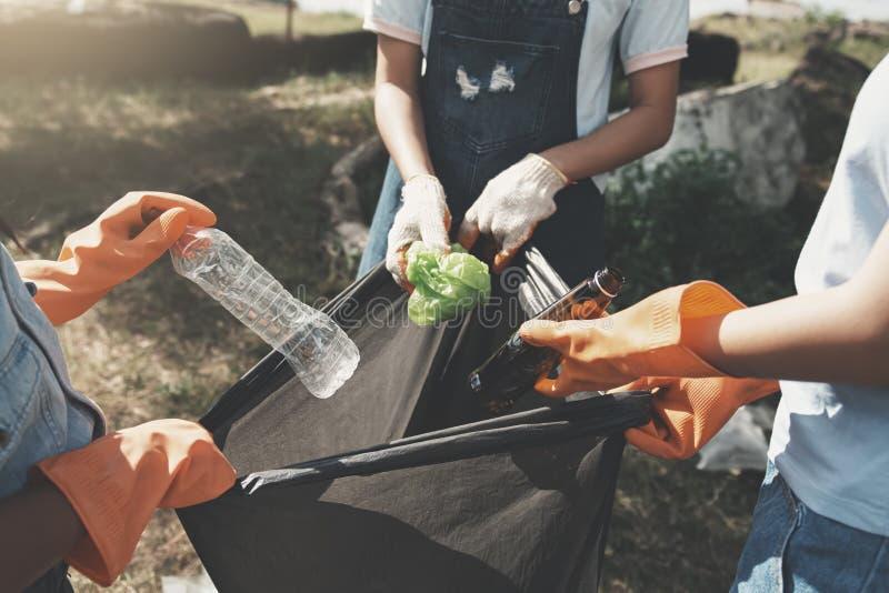mensen die huisvuil opnemen en het zetten in plastic zwarte zak voor het schoonmaken bij park stock afbeelding