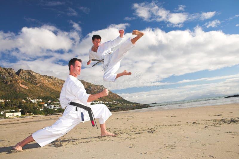 Mensen die Karate op strand uitoefenen stock foto's
