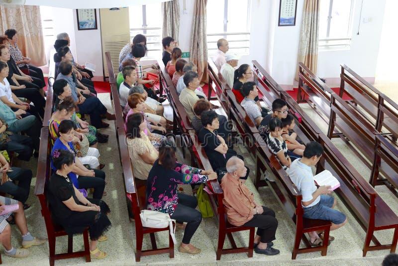 Mensen die in kerk bidden stock afbeeldingen