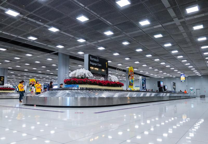 Mensen die Koffer op bagagetransportband wachten bij bagageband bij Suvarnabhumi-Luchthaven Bangkok stock foto's