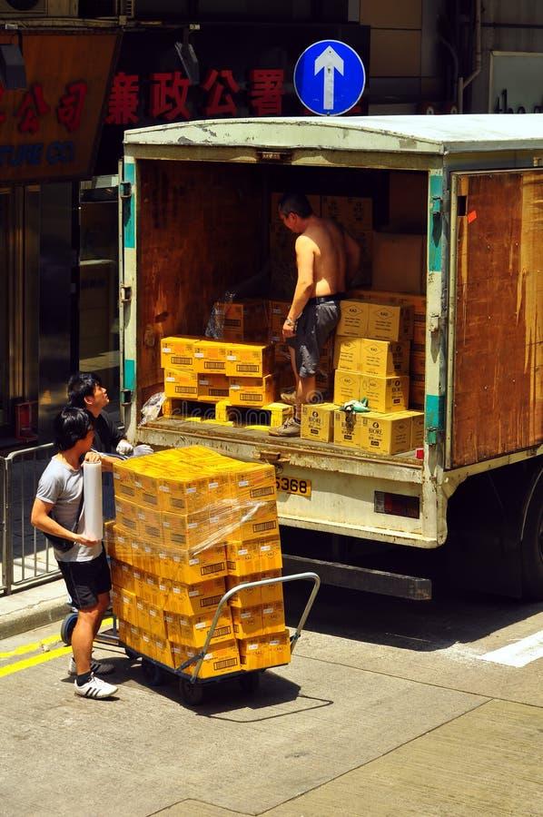 Mensen die lading laden in vrachtwagen stock afbeelding