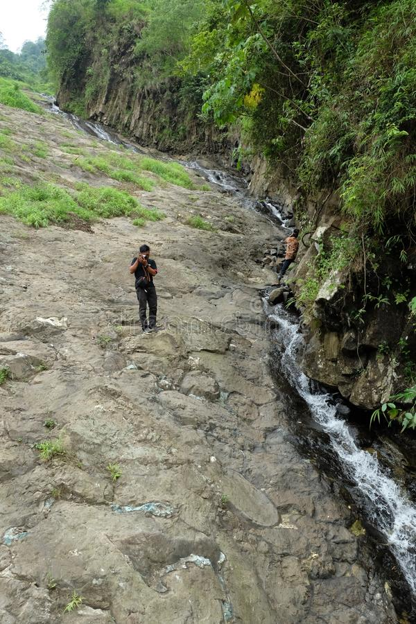 Mensen die landstructuur met kleine riviertrog het waarnemen royalty-vrije stock afbeelding