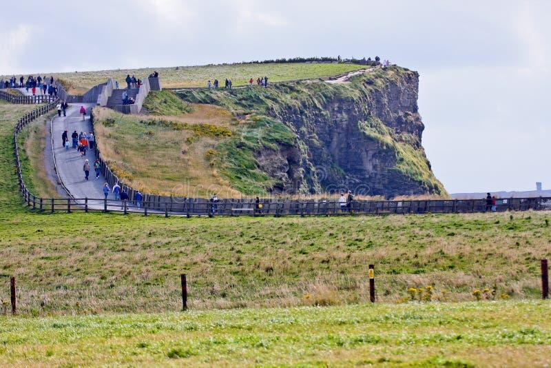 Mensen die langs de Klippen van Moher, Ierland lopen stock foto