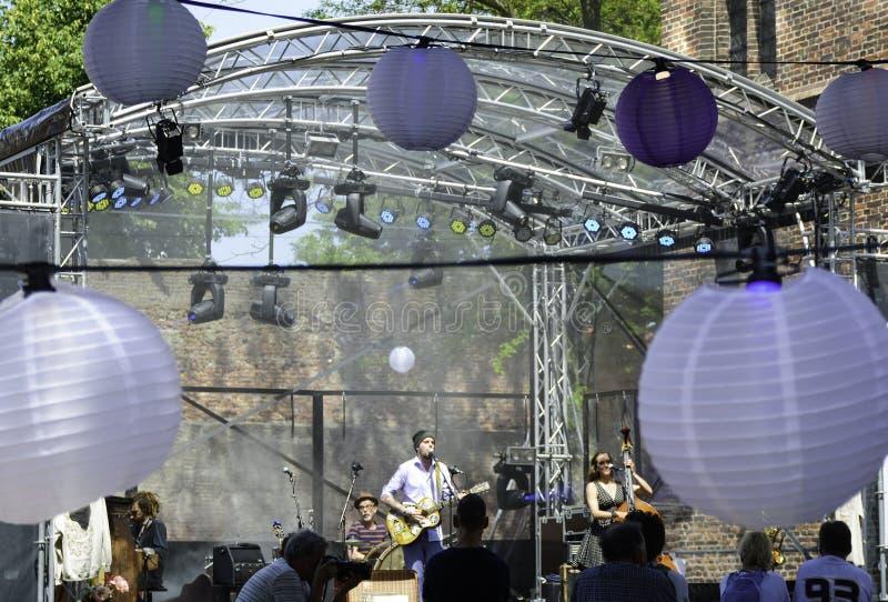 mensen die luisteren naar een concert buitenshuis Prestaties van een muziekband op een podium met licht buitenshuis Buiten stock foto