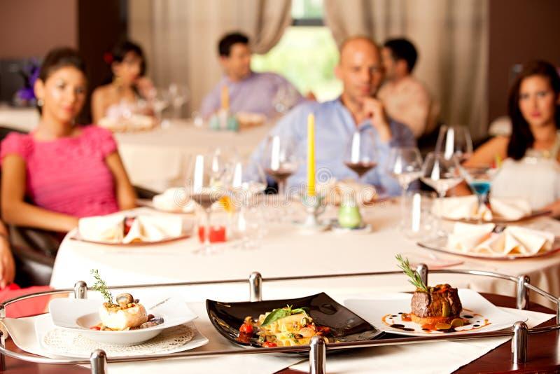 Mensen die maaltijd hebben die in restaurant wordt gediend stock foto's