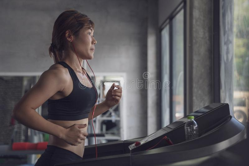 Mensen die in machinetredmolen bij geschiktheidsgymnastiek lopen, Jonge vrouwentraining in gymnastiek gezonde levensstijl, Jonger stock afbeelding