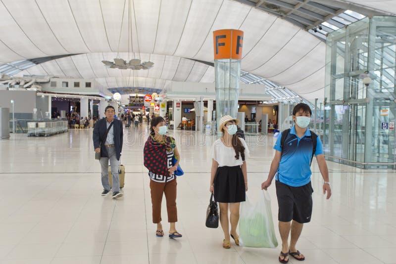 Mensen die maskerbescherming dragen bij de luchthaven royalty-vrije stock afbeeldingen