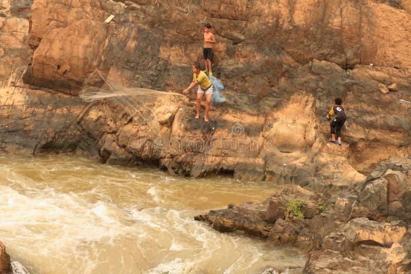 Mensen die met een rudimentair netwerk in de Mekong rivier bij Don Khon-eiland op Laos vissen stock foto
